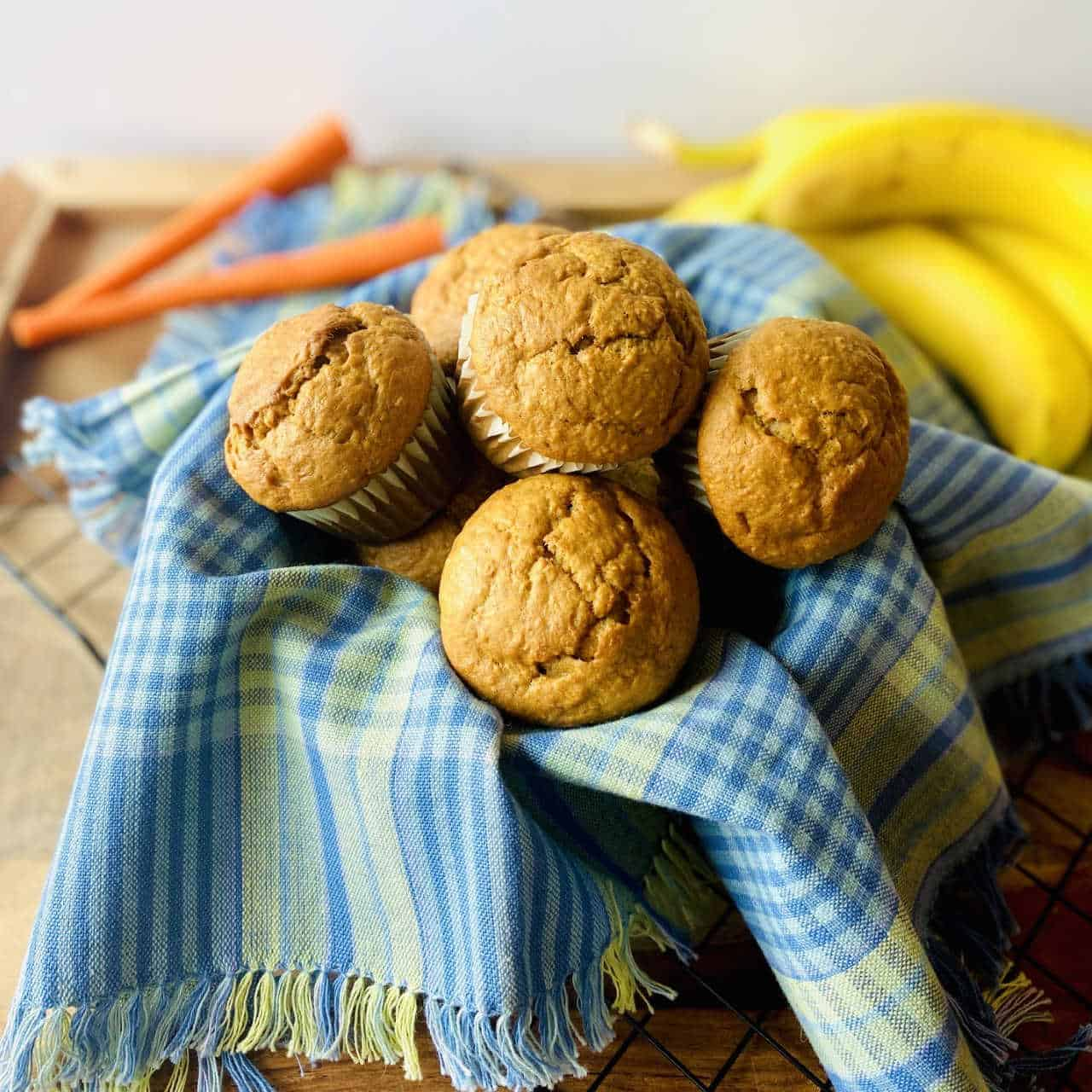banana carrot muffins in basket with carrot and banana in background 2 1 • Kim Schob