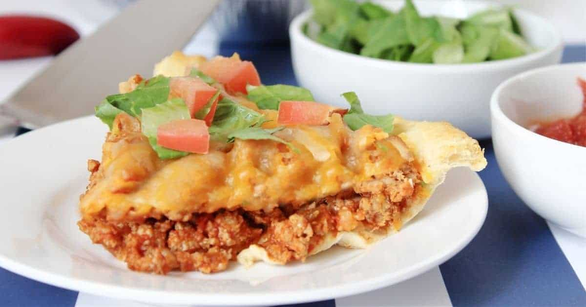 a slice of taco casserole topped with shredded lettuce and tomato