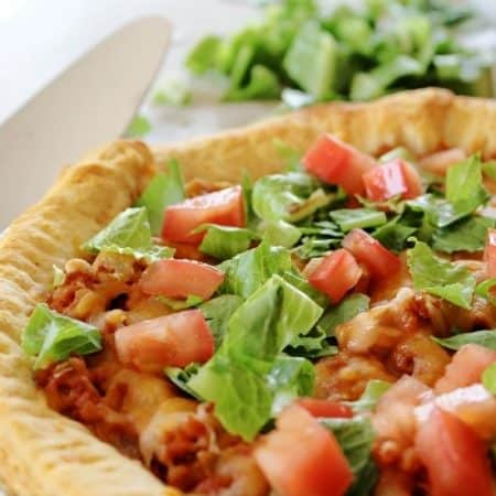 Taco casserole bake with golden crescent roll crust filled with ground beef, topped with cheese and lettuce and tomatoes