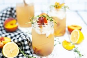 fresh peach gin fizz made with a homemade simple syrup with thyme and honey