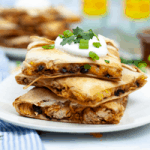sheet pan quesadilla with shredded chicken full of mexican spices served with sour cream