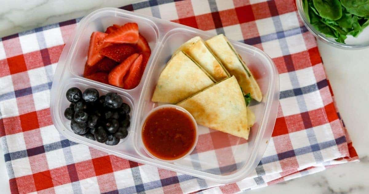 a lunch box is filled with spinach and cheese quesadilla with pizza sauce for dipping