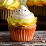 a candy corn cupcake with candy eyes in an orange cupcake wrapper