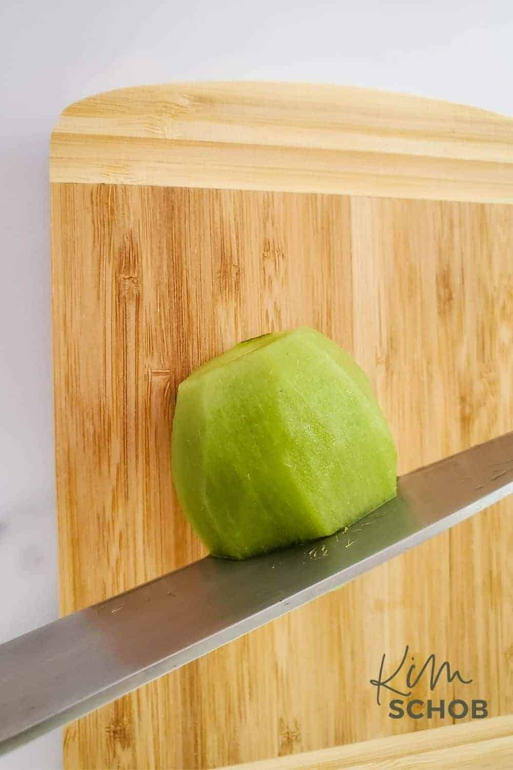 kiwi on a cutting board with a knife in it